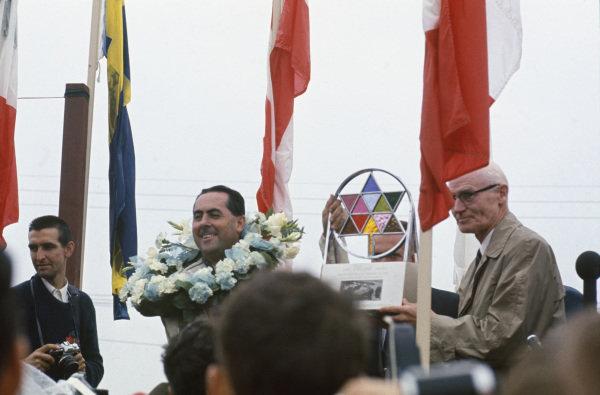 Mosport Park, Ontario, Canada.  25-27 August 1967.  Jack Brabham (Brabham BT24-Repco) celebrates victory on the podium, portrait.  World Copyright: LAT Photographic. Ref:  67CAN09