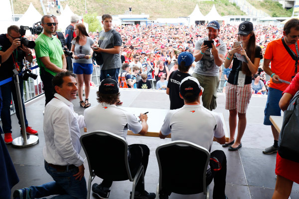 Hockenheim, Germany. Saturday 30 July 2016. Jenson Button, McLaren, and Fernando Alonso, McLaren, sign autographs for fans. World Copyright: Andy Hone/LAT Photographic ref: Digital Image _ONZ7604