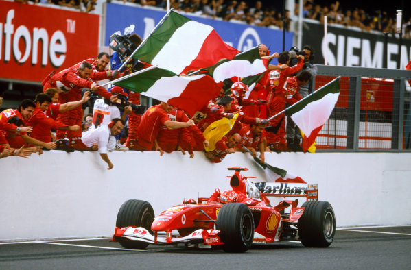 Suzuka , Japan  8th - 10th October 2004Michael Schumacher, Ferrari F2004 is cheered across the line by his team as he takes victory.World Copyright:Charles Coates/LAT Photographic ref: 35mm Image: A17