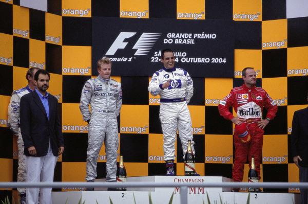 Juan Pablo Montoya celebrates victory on the podium alongside Kimi Räikkönen, 2nd position, and Rubens Barrichello, 3rd position.