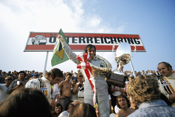 Emerson Fittipaldi celebrates victory on the podium with second place Denny Hulme (R) and third place Peter Revson (L).