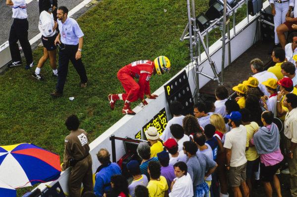 Ayrton Senna leaps over the pitwall.