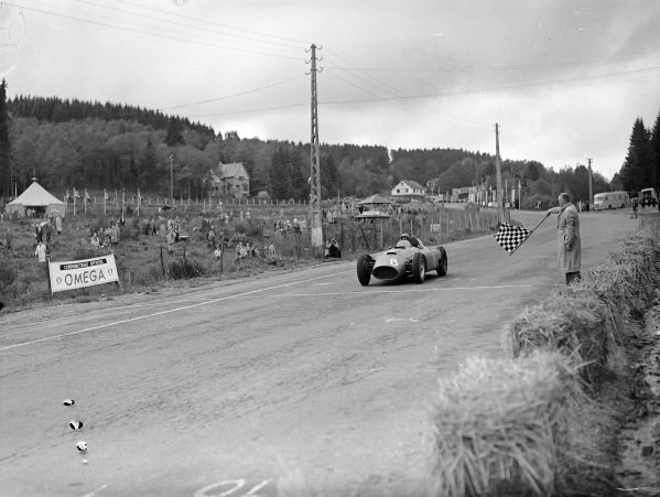 Peter Collins, Ferrari D50, crosses the line to take the chequered flag.