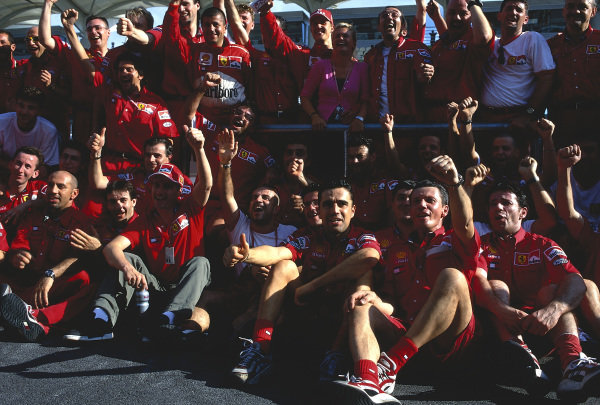 1999 Malaysian Grand Prix.Sepang, Kuala Lumpur, Malaysia. 15-17 October 1999.Eddie Irvine (front) celebrates his 1st position with the Ferrari team and team mate Michael Schumacher (with wife Corinna).Ref-99 MAL 64.World Copyright - LAT Photographic