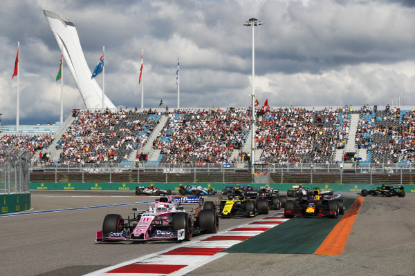 Sergio Perez, Racing Point RP19, leads Nico Hulkenberg, Renault R.S. 19, Max Verstappen, Red Bull Racing RB15, Kevin Magnussen, Haas VF-19, and the remainder of the field at the start
