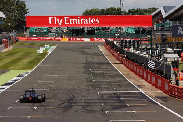 2016 British Grand Prix. Silverstone, Northamptonshire, UK. Sunday 10 July 2016. Lewis Hamilton, Mercedes F1 W07 Hybrid takes the chequered flag as he crosses the finish. World Copyright: Ferraro/LAT Photographic ref: Digital Image _40I5011