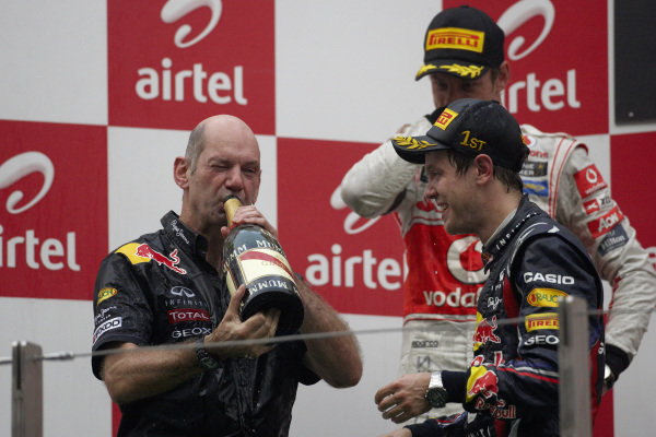 Adrian Newey has a drink of champagne on the podium alongside Sebastian Vettel, 1st position, and Jenson Button, 2nd position.