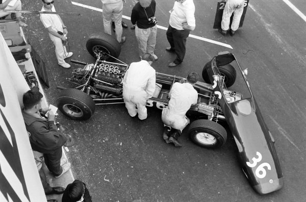 Mike Hailwood's Lotus 25 BRM is worked on by mechanics in the pits.