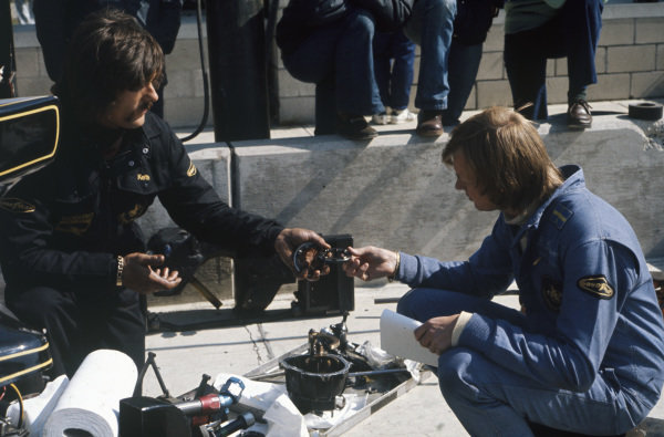 Ronnie Peterson is shown the components of his Lotus 72E Ford by a mechanic.