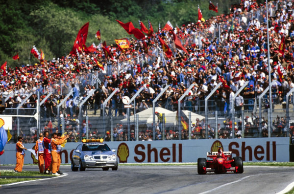 Michael Schumacher, Ferrari F399, punches the air in celebration as marshals and fans applaud him after taking victory. The Mercedes-Benz safety car follows him.