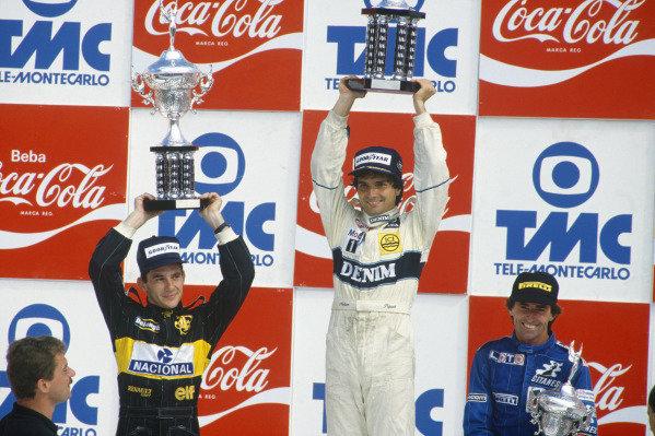 Jacarepagua, Rio de Janeiro, Brazil. 21-23 March 1986. Nelson Piquet (Williams FW11 Honda) 1st position,  Ayrton Senna (Lotus 98T Renault) 2nd position, and Jacques Laffite (Ligier JS27 Renault), celebrate on the podium. Portrait. Ref: 86 BRA 19. World Copyright: LAT Photographic.