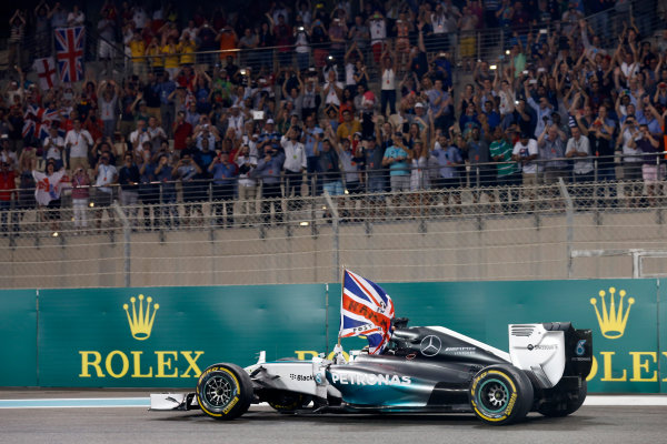 Yas Marina Circuit, Abu Dhabi, United Arab Emirates. Sunday 23 November 2014. Lewis Hamilton, Mercedes F1 W05 Hybrid, 1st Position, drives back to Parc Ferme with his flag raised. World Copyright: Alastair Staley/LAT Photographic. ref: Digital Image _79P0848