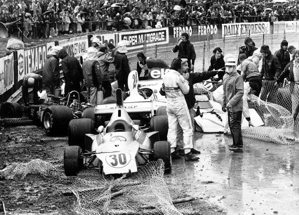1975 British Grand Prix. Silverstone, Great Britain. 17-19 July 1975. The crashed cars of Wilson Fittipaldi (#30 Fittipaldi FD03-Ford Cosworth), James Hunt (#24 Hesketh 308-Ford Cosworth) and Brian Henton (Lotus 72E-Ford Cosworth). Heavy rain caused the race to be stopped early. Accident. World Copyright: LAT Photographic Ref: 7732#33