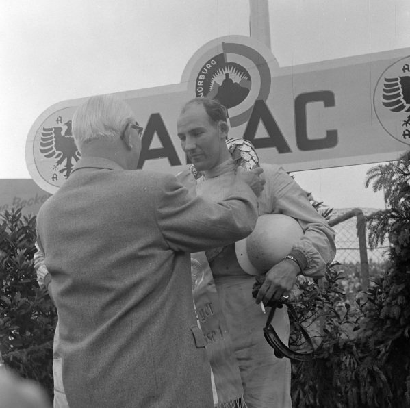 Stirling Moss is presented with the laurel wreath on the podium.