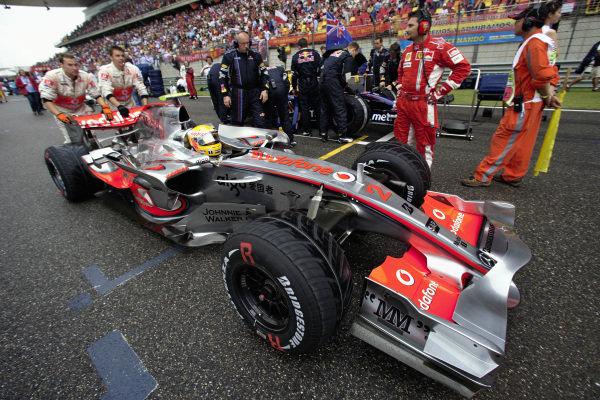 Mechanics push Lewis Hamilton in his McLaren MP4-22 Mercedes to his grid position.