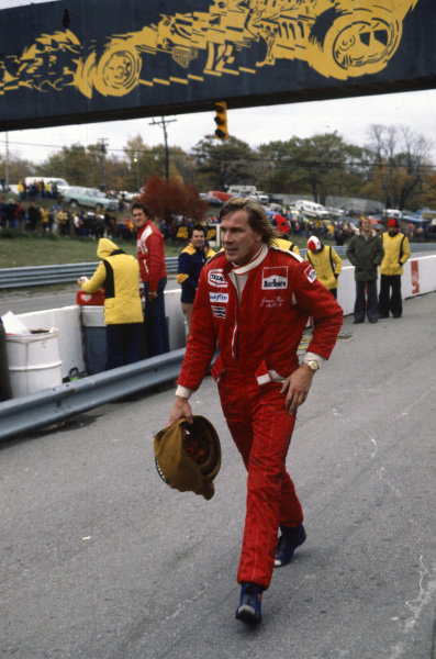 James Hunt walks through the pits.