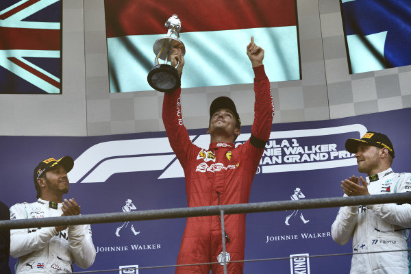 Charles Leclerc, Ferrari, 1st position, lifts his trophy on the podium to applause from Lewis Hamilton, Mercedes AMG F1, 2nd position, and Valtteri Bottas, Mercedes AMG F1, 3rd position