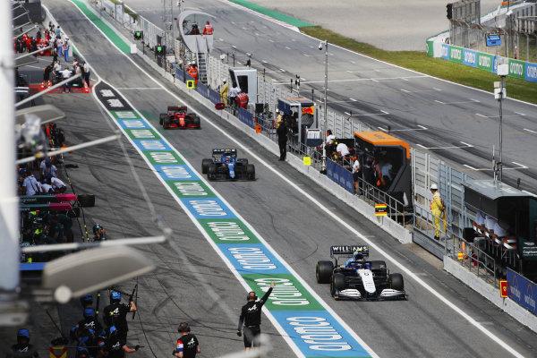 Nicholas Latifi, Williams FW43B, Esteban Ocon, Alpine A521, and Carlos Sainz, Ferrari SF21, in the pit lane