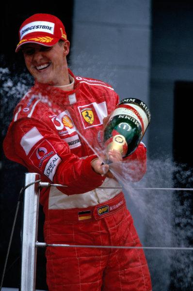 2004 British Grand PrixSilverstone England. 9th - 11th July.Michael Schumacher, Ferrari F2004 celebrates on the podium. World Copyright:Charles Coates/LAT Photographic Ref:35mm image A23