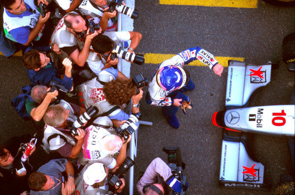 Jerez, Spain.24-26 October 1997.Jacques Villeneuve (Williams Renault) 3rd position celebrates taking the Drivers World Championship title in parc ferme, as the photographers snap away. Ref-97 EUR 27.World Copyright - LAT Photographic