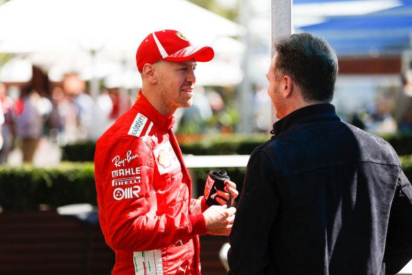 Sebastian Vettel, Ferrari, talks with Christian Horner, Team Principal, Red Bull Racing.