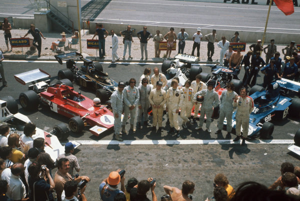 1973 French Grand Prix.  Paul Ricard, Le Castellet, France. 29th June - 1st July 1973.  Graham Hill flicks a v sign for photographers during a driver group photo, alongside (left to right) George Follmer, Wilson Fittipaldi, Emerson Fittipaldi, Carlos Reutemann, Denny Hulme, Jackie Oliver, Ronnie Peterson, Arturo Merzario, Jody Scheckter, Jackie Stewart and Francois Cevert.  Ref: 73FRA79. World Copyright: LAT Photographic