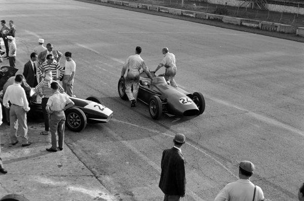 Roy Salvadori's Aston Martin DBR4/250 being pushed by mechanics, while the engine in Jack Fairman's Cooper T45 Maserati is worked on.