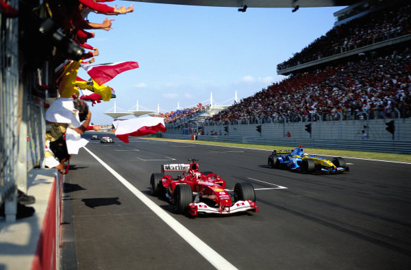 Rubens Barrichello, Ferrari F2004 passes the pit wall where his team celebrate victory ahead of a lapped Jacques Villeneuve, Renault R24.