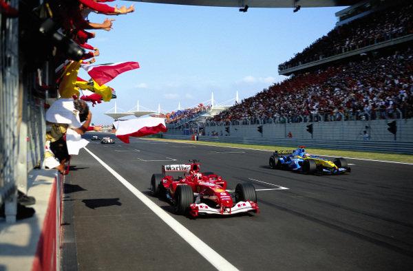 Rubens Barrichello, Ferrari F2004 passes the pit wall where his team celebrate victory ahead of a lapped Jacques Villeneuve, Renault R24.