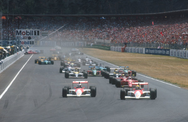 1990 German Grand Prix.Hockenheim, Germany.27-29 July 1990.Ayrton Senna leads teammate Gerhard Berger (both McLaren MP4/5B Honda's) into the Nordkurve, followed by Alain Prost, Nigel Mansell (both Ferrari 641's), Riccardo Patrese, Thierry Boutsen (both Williams FW13B Renault's), Nelson Piquet, Alessandro Nannini (both Benetton B190 Ford's), Jean Alesi (Tyrrell 019 Ford), Ivan Capelli (Leyton House CG901 Judd) and Aguri Suzuki (Lola 90 Lamborghini) at the start. In the background Emanuele Pirro (Dallara 190 Ford) hits the pit wall after colliding with David Brabham and involving Philippe Alliot (Ligier JS33B Ford/behind him).Ref-90 GER 04 .World Copyright - LAT Photographic