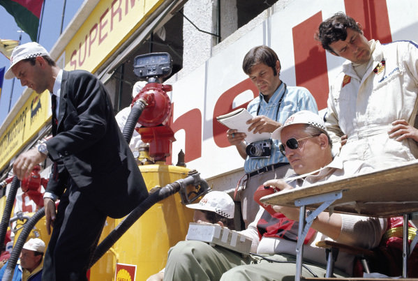 Porsche's legendary engineer Helmuth Bott takes the times, Ferdinand Piech is about to jump from the pitwall. Journalist Helmut Zwickl stands in the middle while Porsche driver Brian Redman reads the schedules.