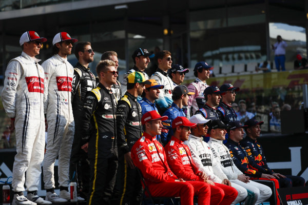 The class of 2019 pose for a final group photo. Back row L-R: Kimi Raikkonen, Alfa Romeo Racing, Antonio Giovinazzi, Alfa Romeo Racing, Romain Grosjean, Haas F1, Kevin Magnussen, Haas F1, Robert Kubica, Williams Racing, George Russell, Williams Racing, Sergio Perez, Racing Point, Lance Stroll, Racing Point. Middle row, L-R: Nico Hulkenberg, Renault F1 Team, Daniel Ricciardo, Renault F1 Team, Carlos Sainz Jr., McLaren MCL34, Lando Norris, McLaren, Pierre Gasly, Toro Rosso, and Daniil Kvyat, Toro Rosso. Middle row, L-R: Charles Leclerc, Ferrari, Sebastian Vettel, Ferrari, Lewis Hamilton, Mercedes AMG F1, Valtteri Bottas, Mercedes AMG F1, Max Verstappen, Red Bull Racing and Alexander Albon, Red Bull Racing