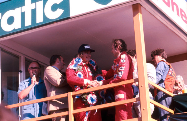 1976 British Grand Prix.Brands Hatch, England.16-18 July 1976.James Hunt (McLaren Ford) 1st position, (later disqualified) shakes hands with championship rival Niki Lauda (Ferrari) 1st position on the podium.Ref-76 GB 21.World Copyright - LAT Photographic